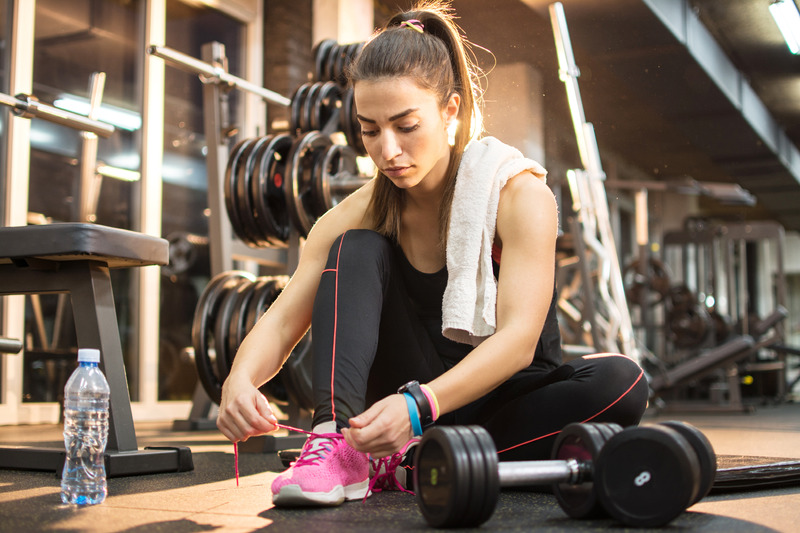 woman tying her indoor gym shoes